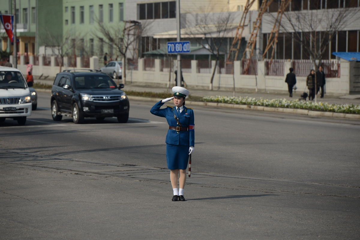 A transit controler salutes as a bus with journalists drives by in Pyongyang on April 11, 2012