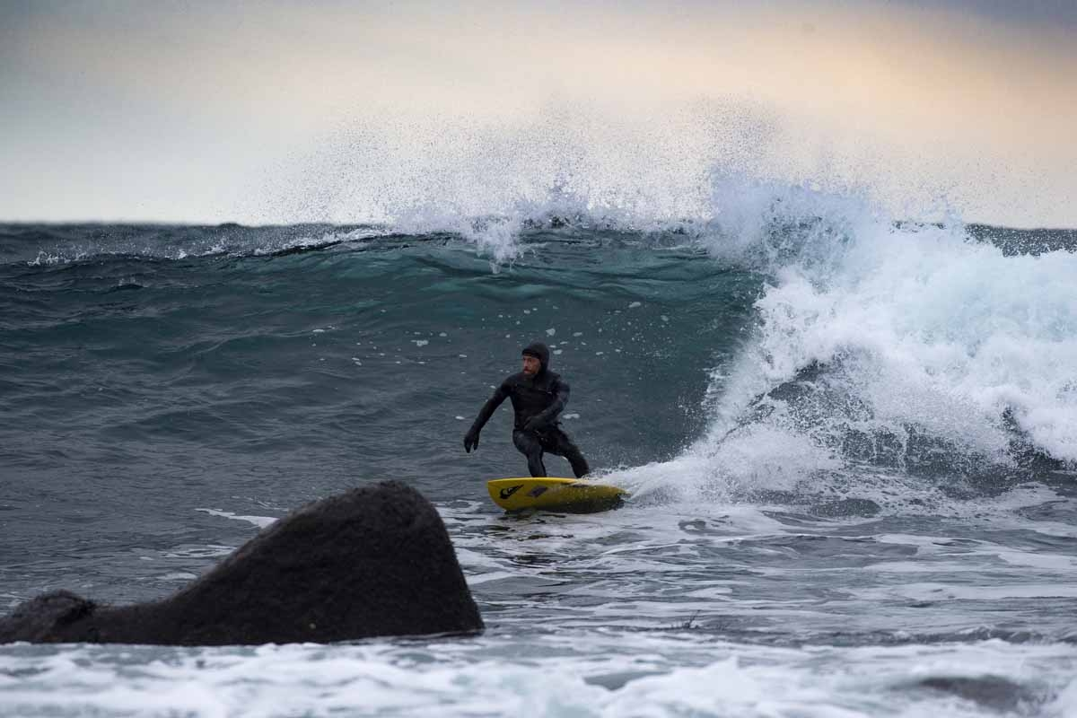 Australian surf legend from the 80's Tom Carroll, 55, rides a wave in Unstad above the Arcic Circle on March 10, 2017. / AFP PHOTO / OLIVIER MORIN