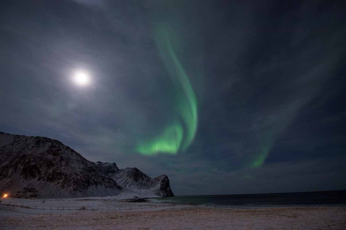 The Northern Lights, also known as 'Aurora borealis' flash across the sky above Unstad, a town know for being the world's most northern artic surf school on March 7, 2017. / AFP PHOTO / OLIVIER MORIN