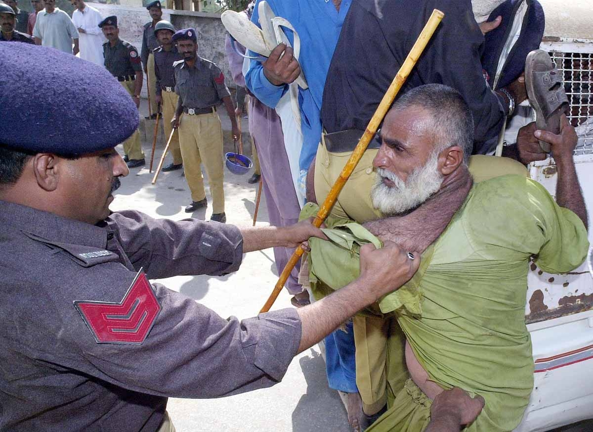Pakistani policemen try to drag an elderly protestor in a bid to foil a demonstration in Jacobabad city, 500 kilometers northeast of Karachi, 23 October 2001.