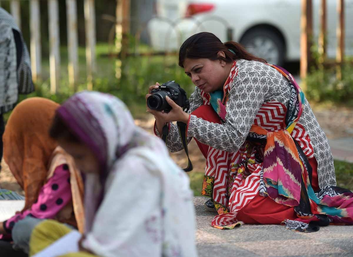 In this photograph taken on August 30, 2016,  Shazia Bhatti, a Pakistani 38-year old journalist shoots video footage during an assignment in Islamabad.