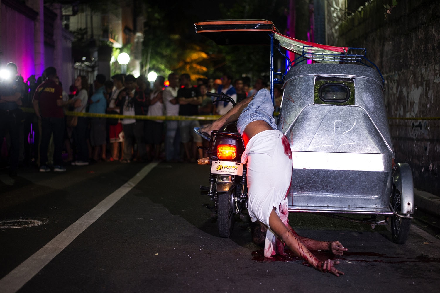 Bystanders watch the dead body of a tricycle driver shot by gunmen in Manila on July  22, 2016