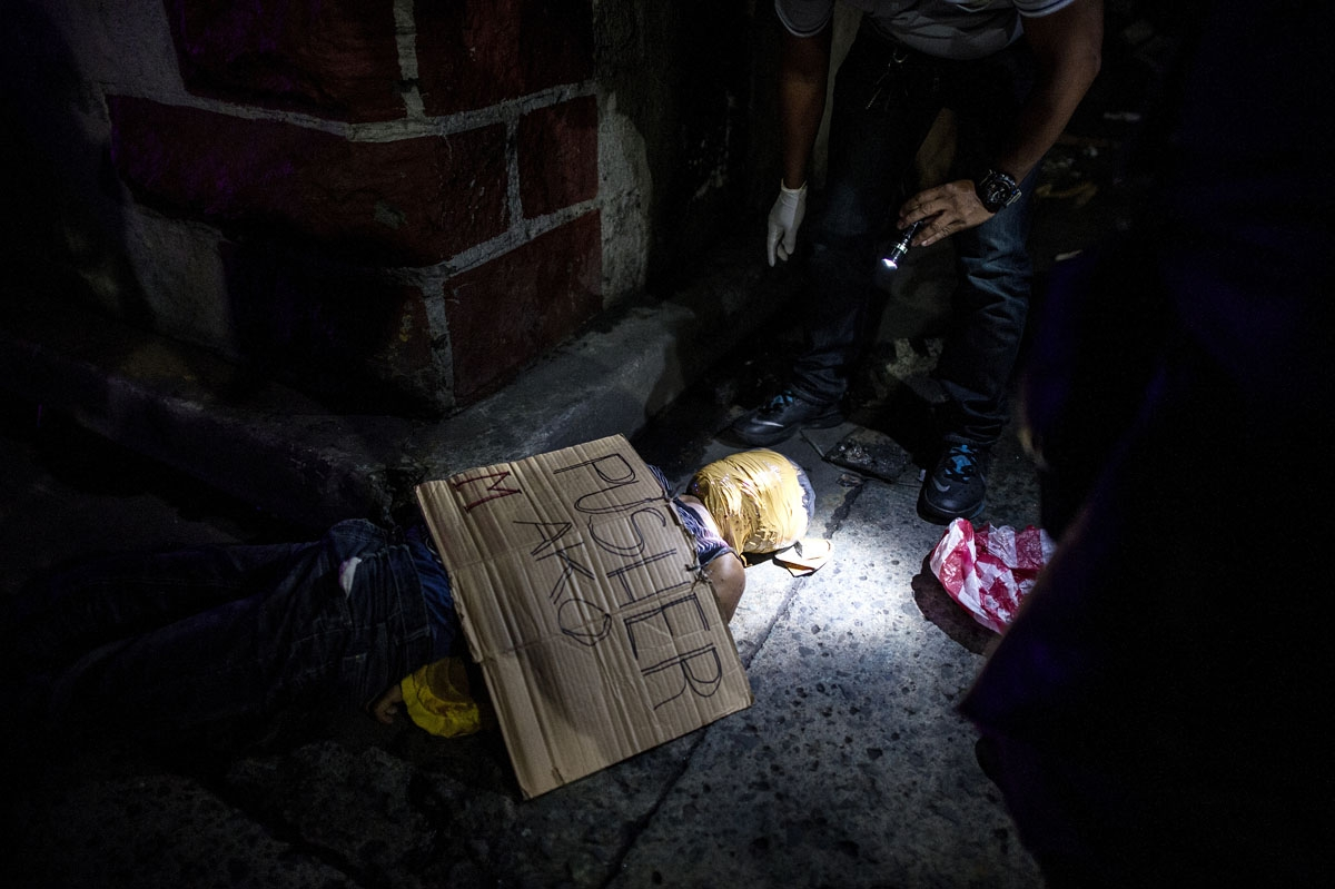 This photo taken on July 8, 2016 shows police officers investigating the body of an alleged drug dealer with his face covered with packing tape, with a cardboard sign on him reading I'm a pusher, at a street in Manila.