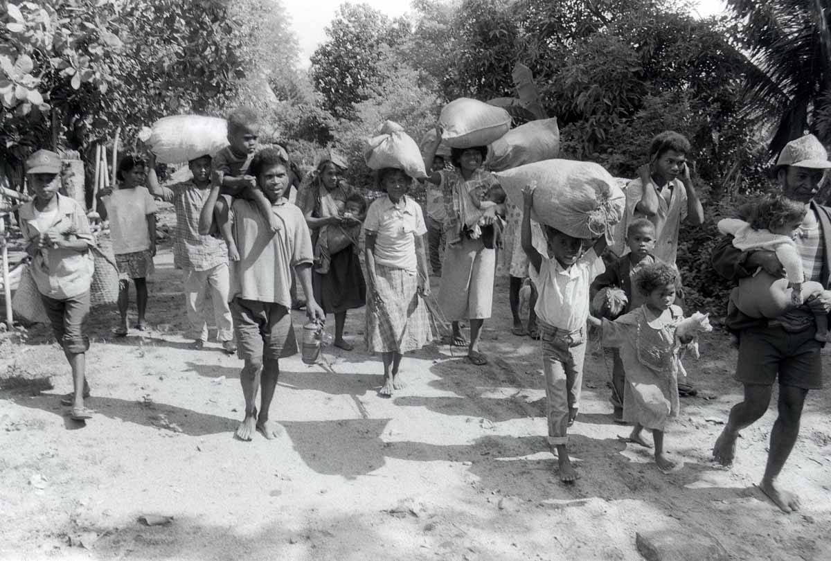 Aeta tribes-people flee their village with their meager belongings, 11 June 1991, in Botolan, which is within the 20-kilometer (12.4 miles) danger zone radius from the erupting Mount Pinatubo volcano.