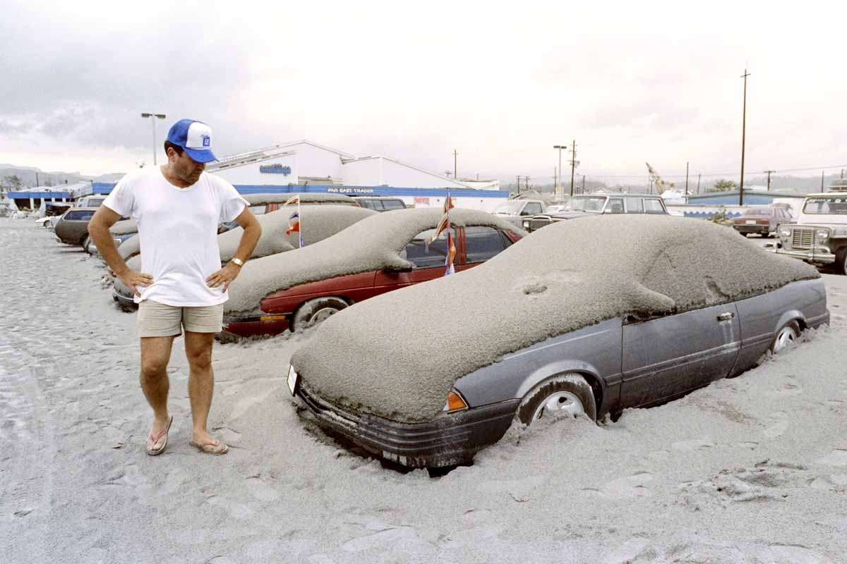 A US Navy personnel looks at his volcanic ash covered car at the Subic Naval Base parking lot, on June 19, 1991