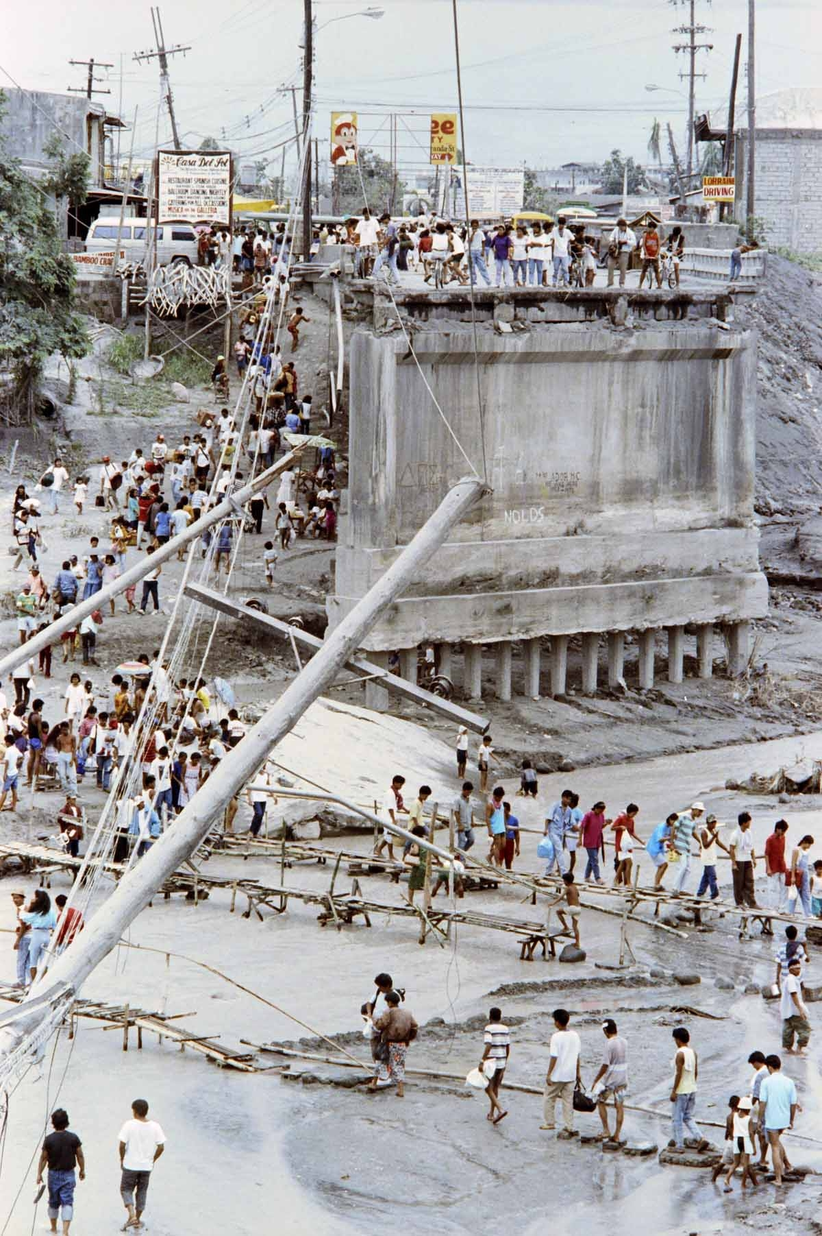 Angeles City residents cross the river on improvised wooden bridges, on June 20, 1991 after Abacan was destroyed by flash flood and mudflows from combined effects of typhon, eruption of Mount Pinatubo volcano and earthquakes
