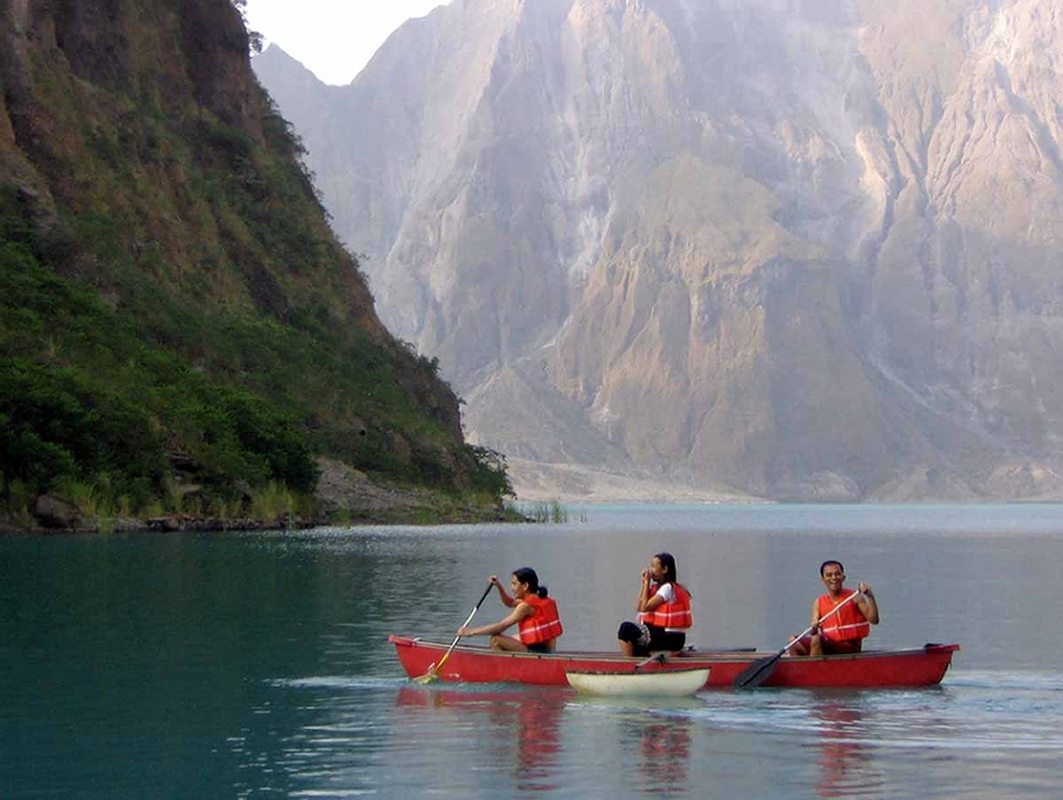 Local tourists use a kayak to explore the turquoise-colored crater lake of Mount Pinatubo volcano 29 April 2006.