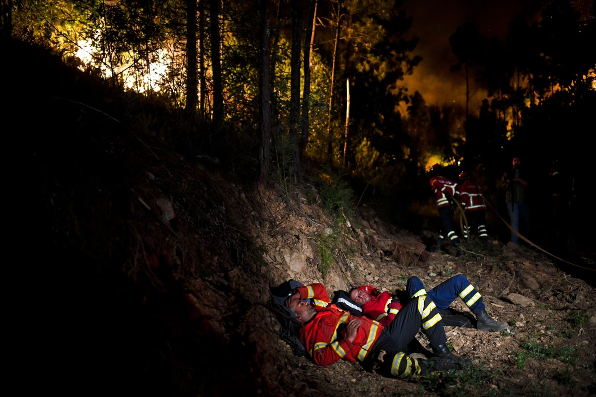 Firefighters rest during a wildfire at Penela, Coimbra, central Portugal, on June 18, 2017.