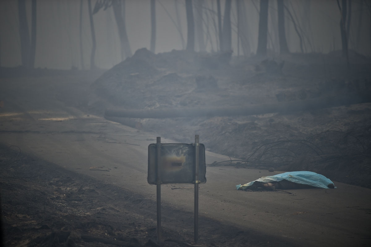 The dead body of a victim of a wildfire lies covered by a blanket on a road in Pedrogao, on June 18, 2017.