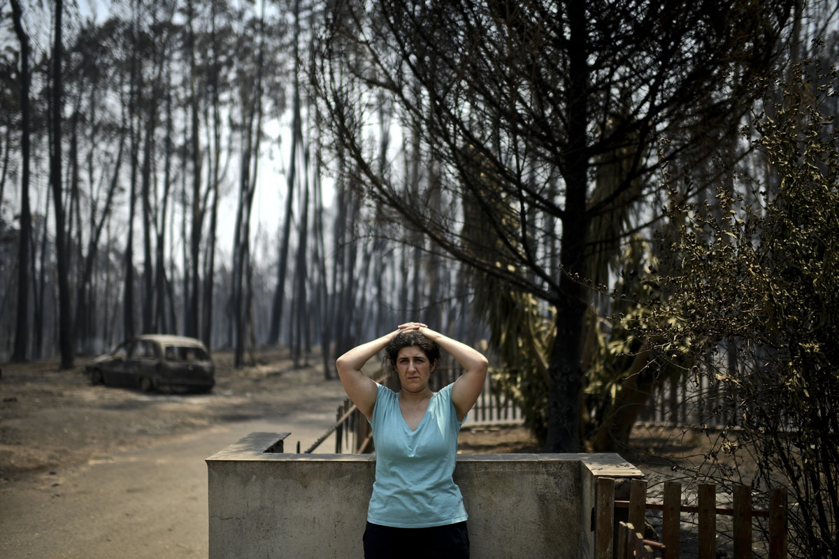 Anabela Silva stands in front of her house with her burnt car in the background after a wildfire in Figueiro dos Vinhos on June 18, 2017.