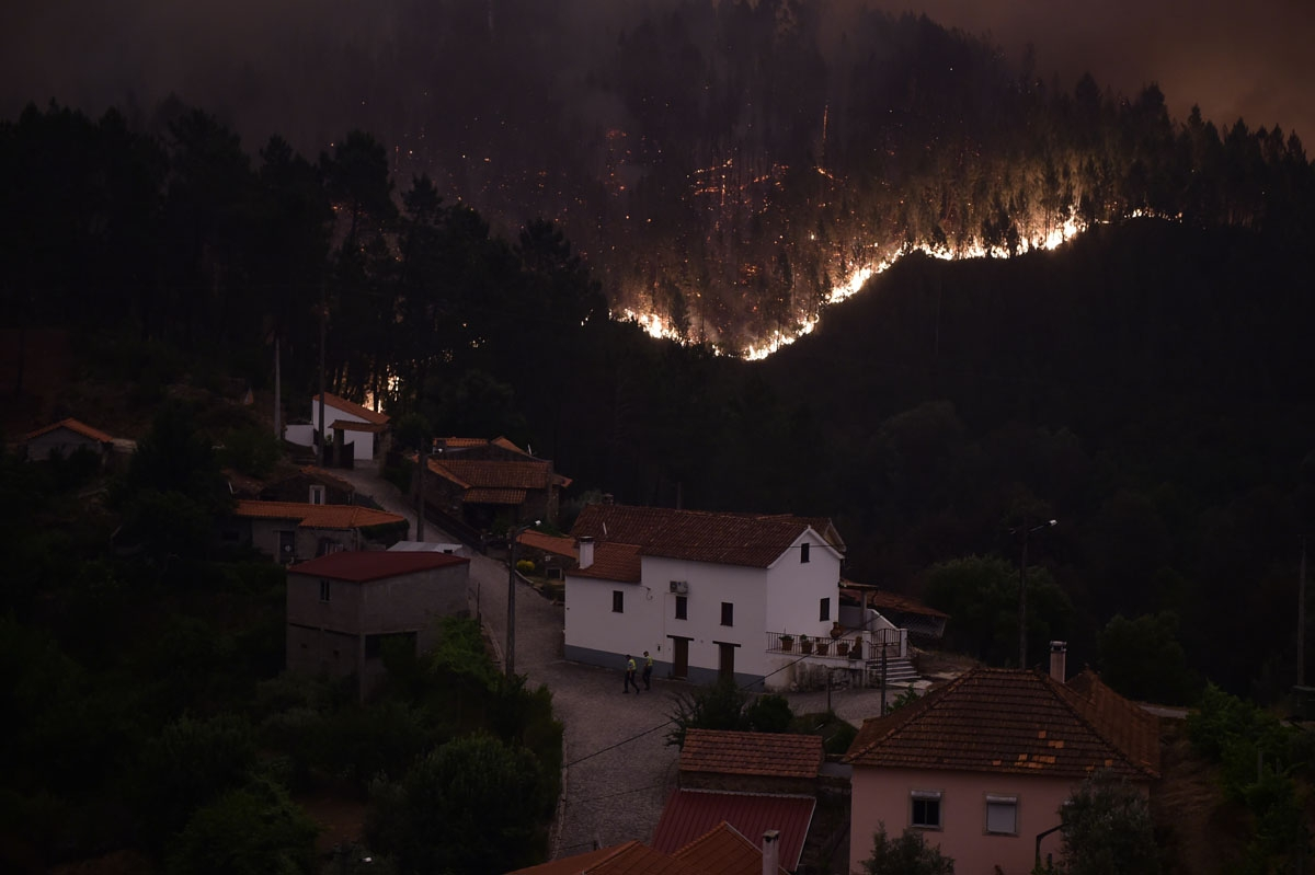 A picture taken on June 18, 2017 shows flames and smoke during a wildfire near the village of Mega Fundeira.