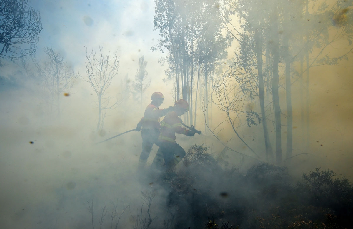 Firefighters use a hose to combat a wildfire in Vale da Ponte, Pedrograo Grande, on June 20, 2017.