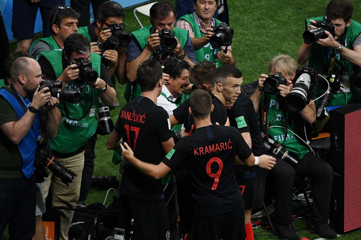Croatia's forward Mario Mandzukic (C-L) and Croatia's midfielder Ivan Rakitic (C2R) speak to AFP photographer Yuri Cortez (C) after falling on him with teammates while celebrating their second goal during the Russia 2018 World Cup semi-final football matc