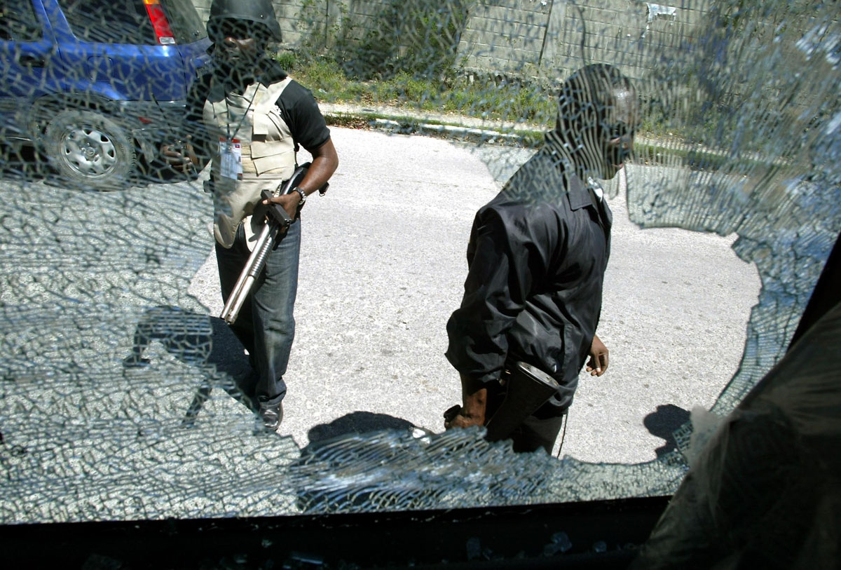 Haitian police are seen through a broken car window 29 February 2004 in Port-au-Prince.  Angry mobs rampaged through the Haitian capital  after President Jean Bertrand Aristide fled the country, leaving smoke billowing over the city and at least 10 dead.