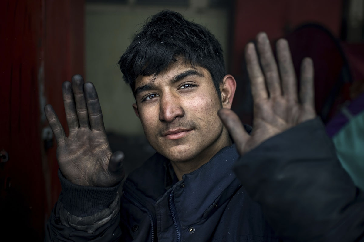 A migrant shows his hands while eating a meal provided by volunteers, outside of derelict warehouses used as a makeshift shelter, in Belgrade on January 11, 2017, as temperatures drop to -15 degrees Celsius in the evening.