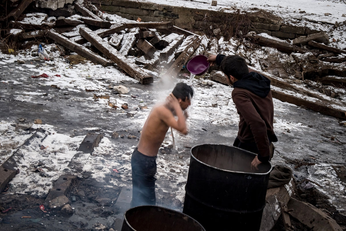 A migrant washes himself outside a derelict warehouse used as a shelter near Belgrade's main railway station on January , 2017, with temperatures bellow zero Celsius.