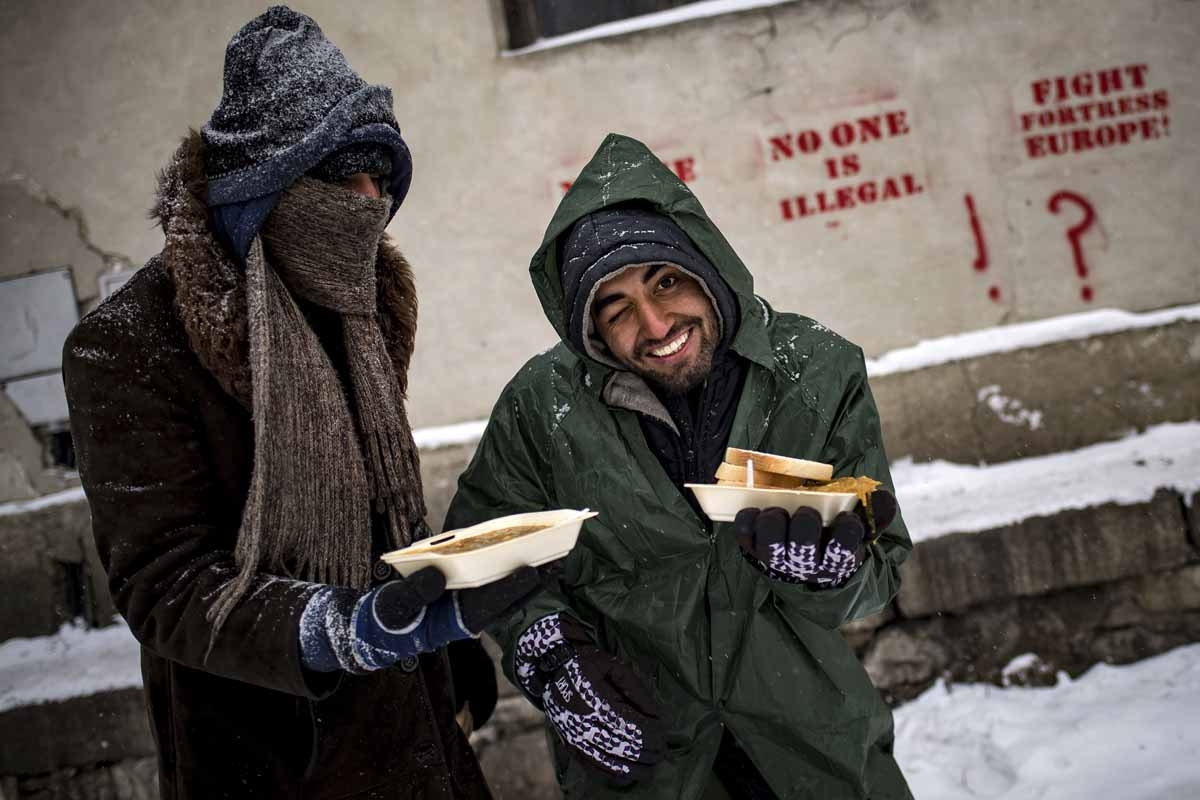 Migrants receive hot meals from volunteers, outside of derelict warehouses which they use as a makeshift shelter, in Belgrade on January 11, 2017, as temperatures dropped to -15 degrees Celsius overnight.