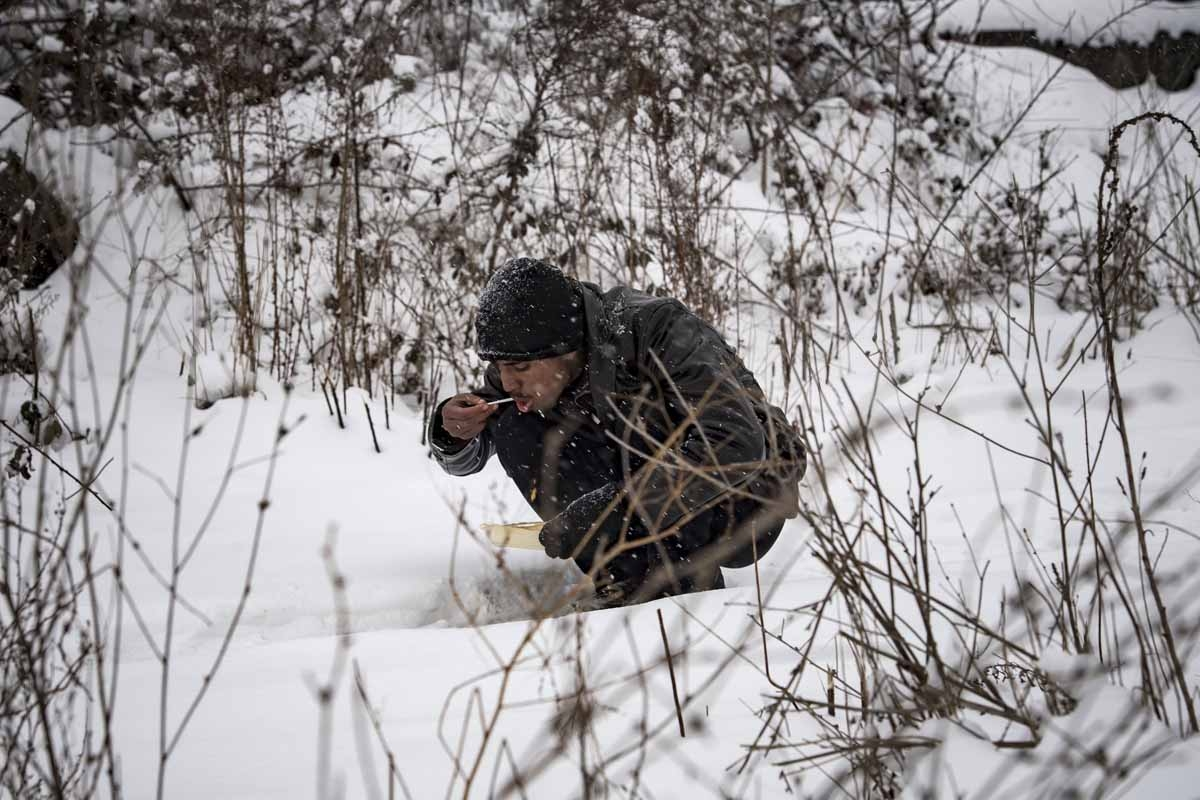 A migrants eats his meal while sitting in the snow in Belgrade on January 11, 2017, as temperatures drop to -15 degrees Celsius in the evening.