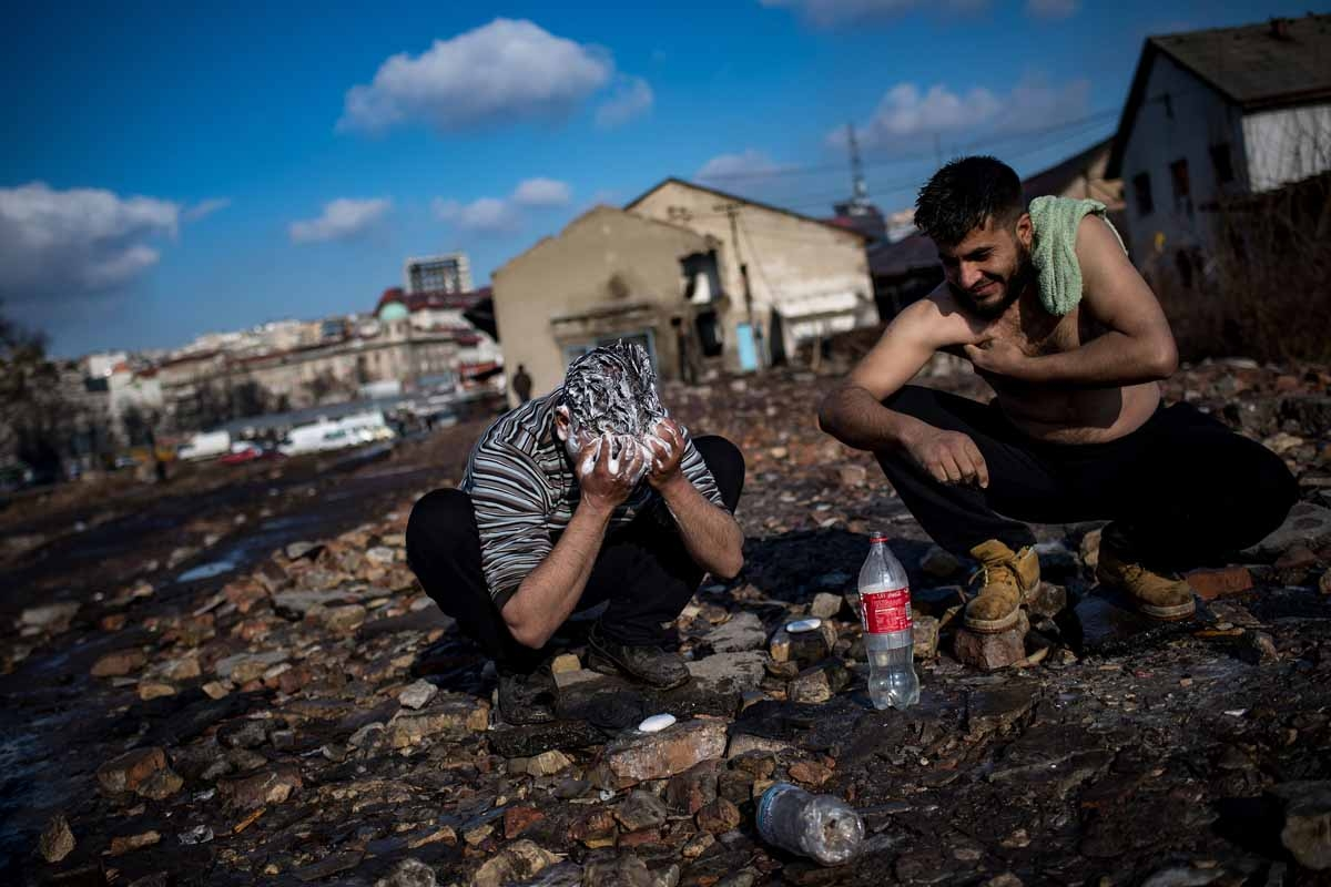 Migrants wash themselfs outside of derelict warehouses which they use as a makeshift shelter in Belgrade on January 15, 2017, with temperatures just bellow zero Celsius overnight.