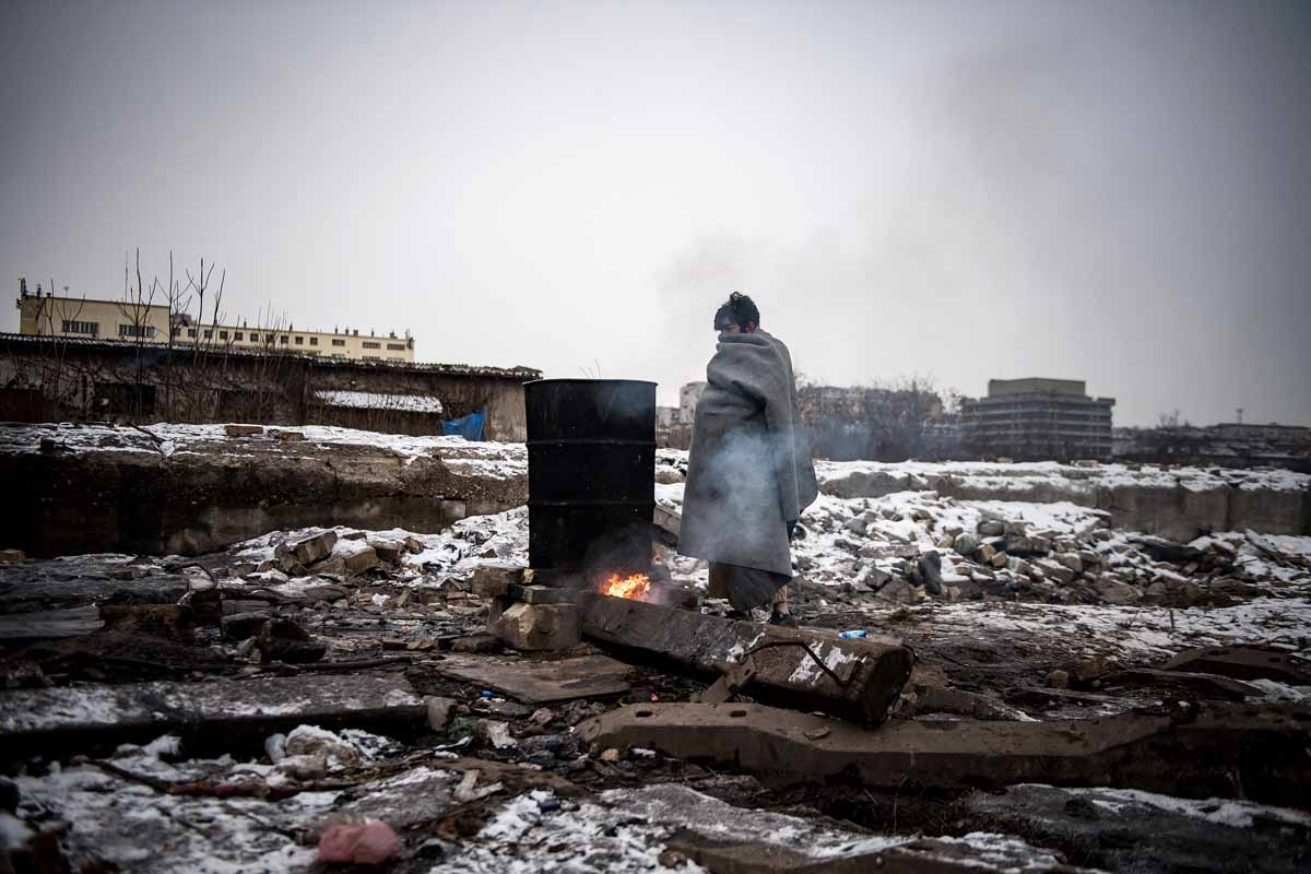 A migrant warms up next to a fire outside a derelict warehouse used as a shelter near Belgrade's main railway station on January 17, 2017, with temperatures bellow zero Celsius.