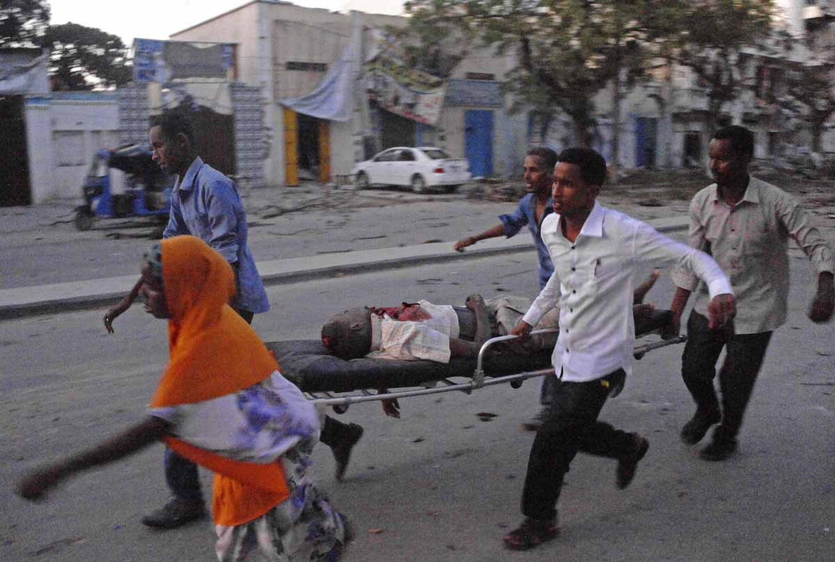 People carry a victim of a terror attack at the Ambassador Hotel, after Somalia's Al-Qaeda-linked Shabaab on June 1, 2016, launched a deadly attack on a top Mogadishu hotel popular with MPs, setting off a car bomb and fighting security forces inside the c