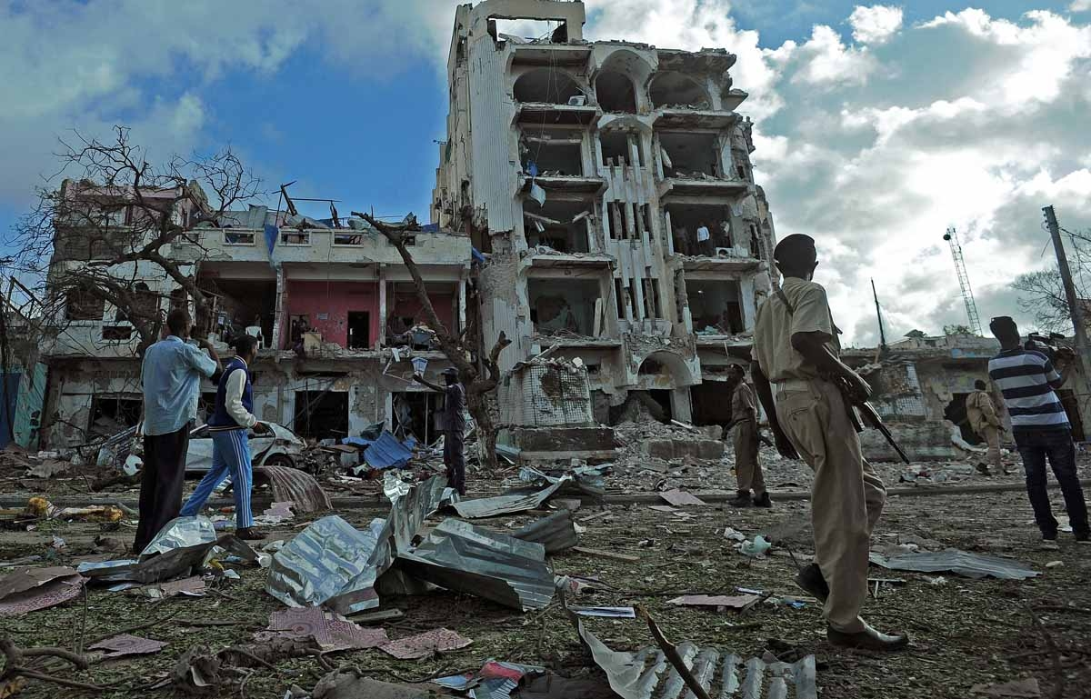 People stand on the scene of a terror attack outside The Ambassador Hotel in Mogadishu on June 2, 2016.