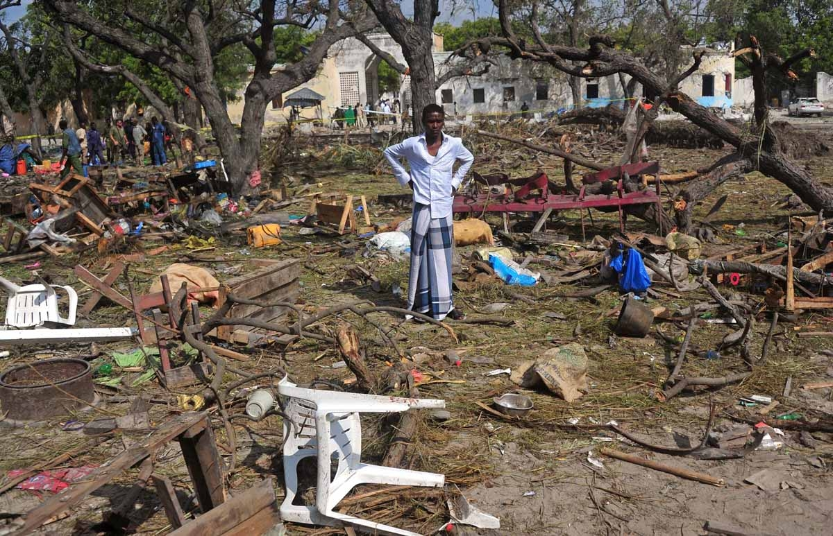 A man stands amongst scattered objects and belongings at the scene of a car bomb attack near the port of the capital Mogadishu, on December 11, 2016.