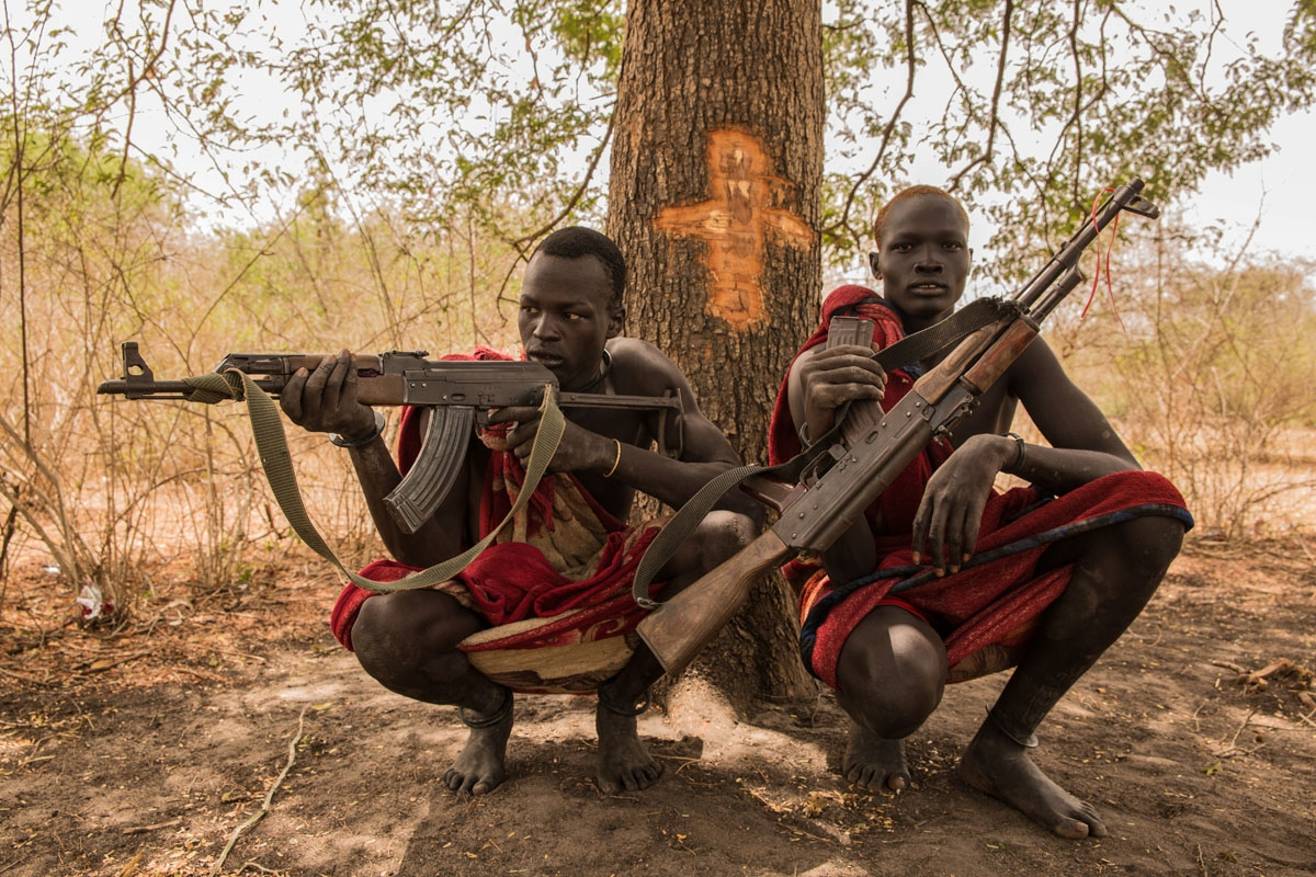 Sudanese cattle keepers from Dinka tribe Makal Maker (R) and Achiek Butich pose with the guns for their protection at their cattle camp in Mingkaman, Lakes State, South Sudan, on March 2, 2018.