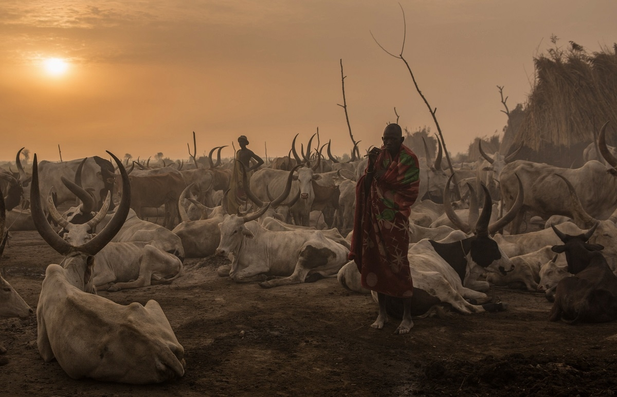 A Sudanese man from Dinka tribe stands in the early morning at their cattle camp in Mingkaman, Lakes State, South Sudan, on March 3, 2018.