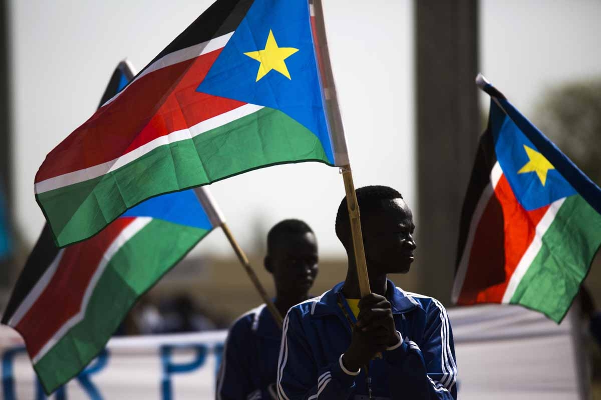 Football players holding South Sudanese flags march at the Juba Stadium, as part of the closing ceremony of the National Unity Day events in Juba, South Sudan, on January 23, 2016.