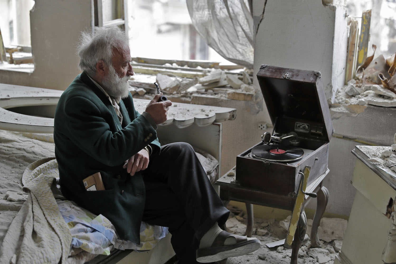 Mohammad Mohiedine Anis, 70, smokes his pipe as he sits in his destroyed bedroom listening to music on his vinyl player, gramophone, in Aleppo's formerly rebel-held al-Shaar neighbourhood on March 9, 2017. / AFP PHOTO / JOSEPH EID