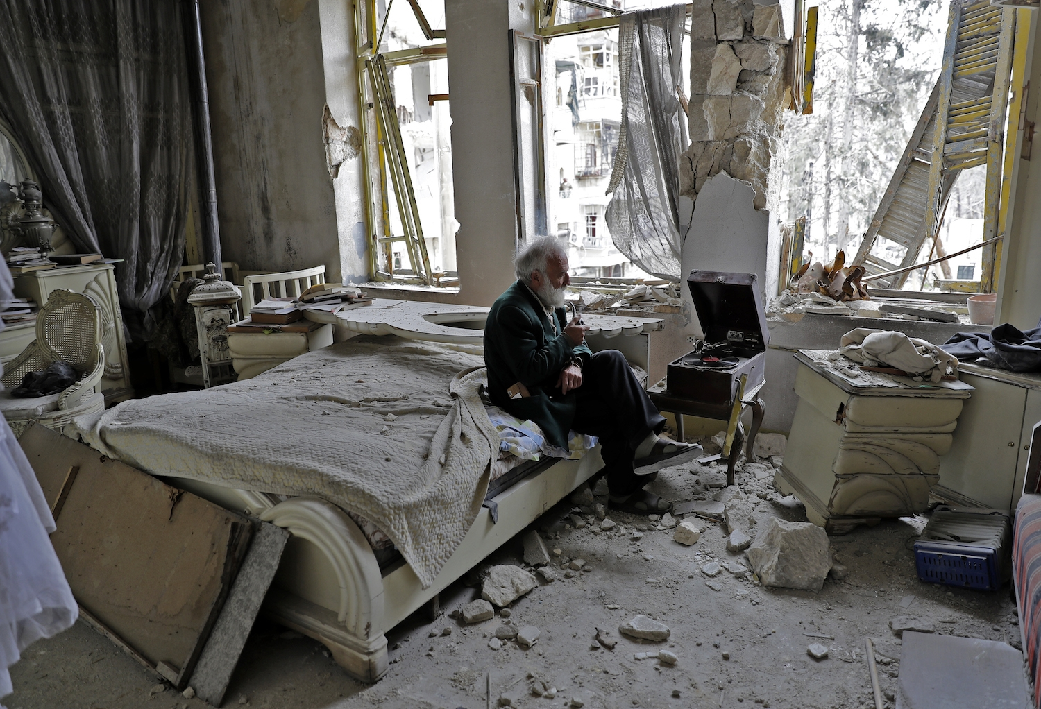 Mohammad Mohiedine Anis, 70, smokes his pipe as he sits in his destroyed bedroom listening to music on his vinyl player, gramophone, in Aleppo's formerly rebel-held al-Shaar neighbourhood.  / AFP PHOTO / JOSEPH EID