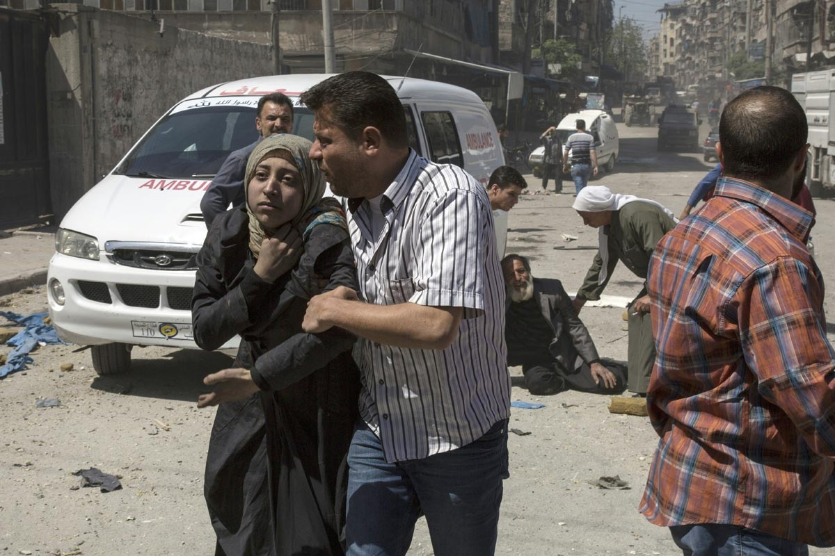 People in a state of shock receive help on a street following a reported airstrike on April 23, 2016 in the rebel-held neighbourhood of Tareeq al-Bab in the northern city of Aleppo