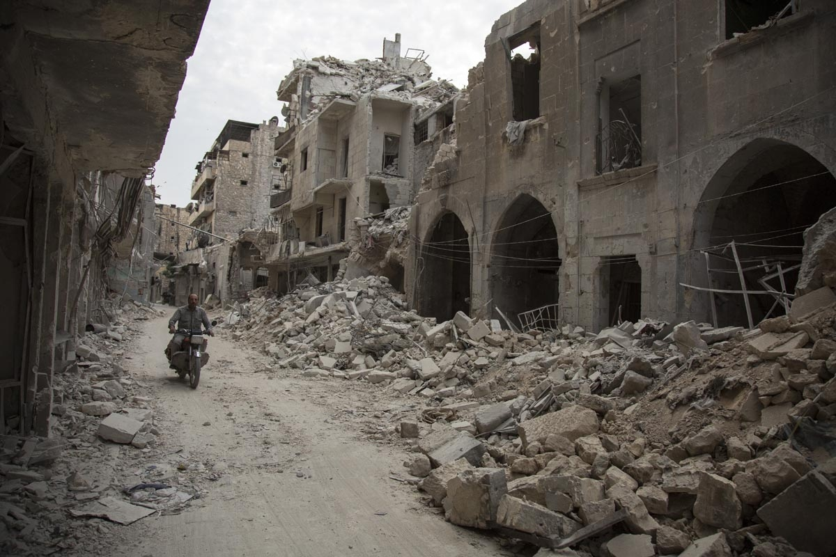 A Syrian man rides his motorbike past destroyed buildings on May 2, 2016, in Aleppo's Bab al-Hadid neighbourhood which was targeted recently by regime air strikes