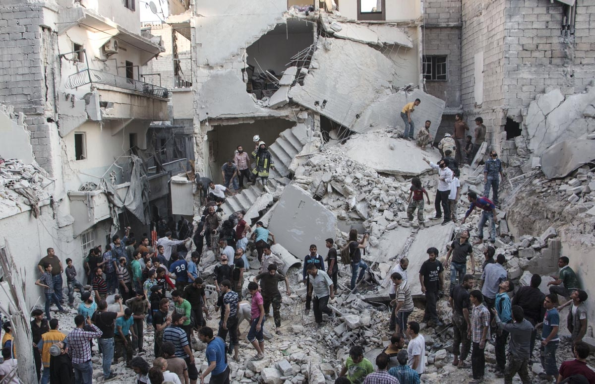 People gather at the scene after Syrian government forces allegedly dropped barrel bombs on the northern Syrian city of Aleppo, on May 30, 2015