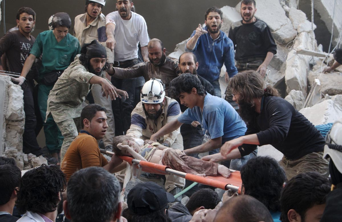 Syrian rescue workers and citizens carry a child on a stretcher from a building following a reported barrel bomb attack by Syrian government forces at the Al-Firdaws neighbourhood of the northern Syrian city of Aleppo, on May 30, 2015