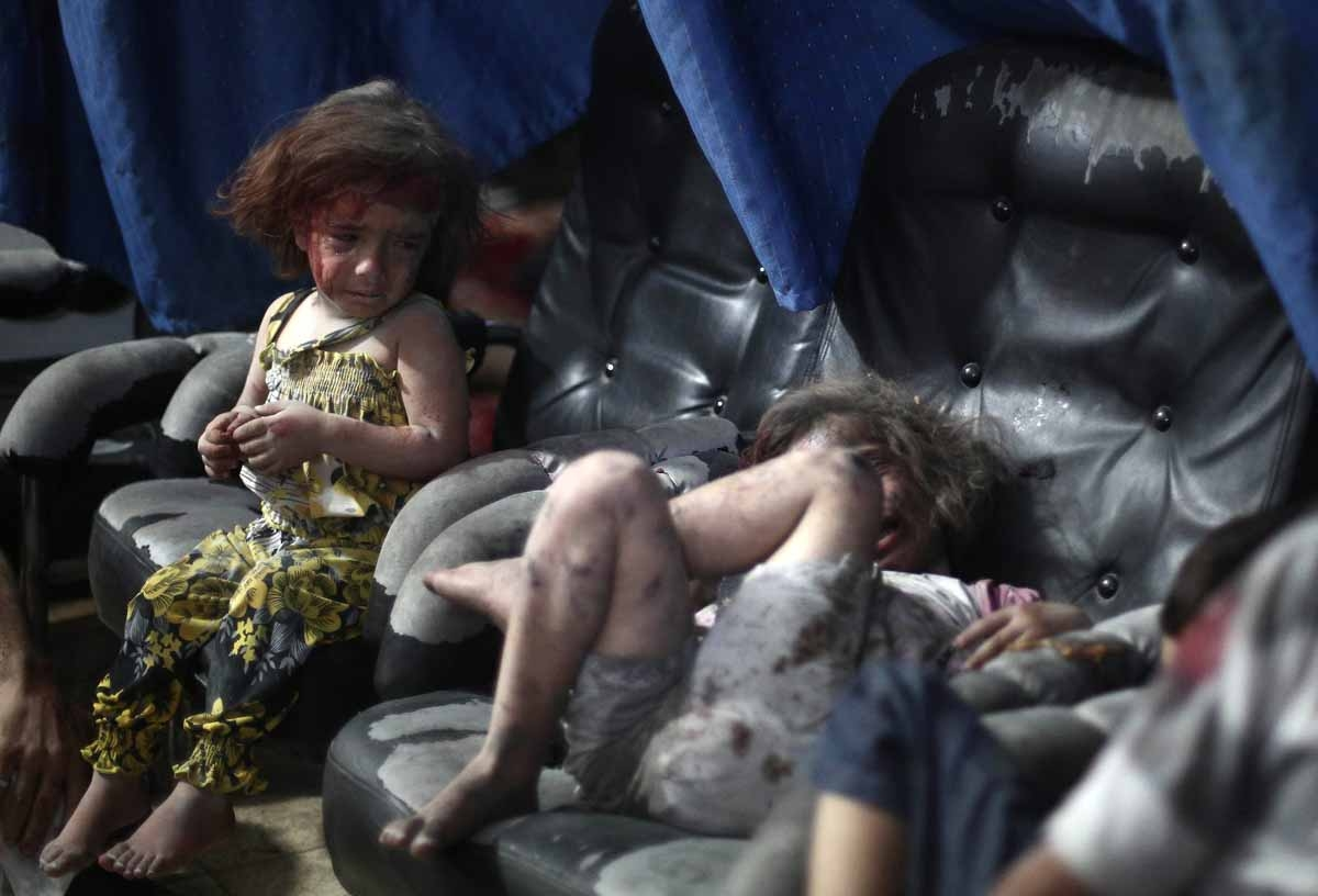 A wounded Syrian child cries looking on at another wounded girl, as they wait for treatment, at a makeshift hospital in the rebel-held town of Douma near Damascus on September 11, 2014, after reported airstrikes by Syrian government forces.