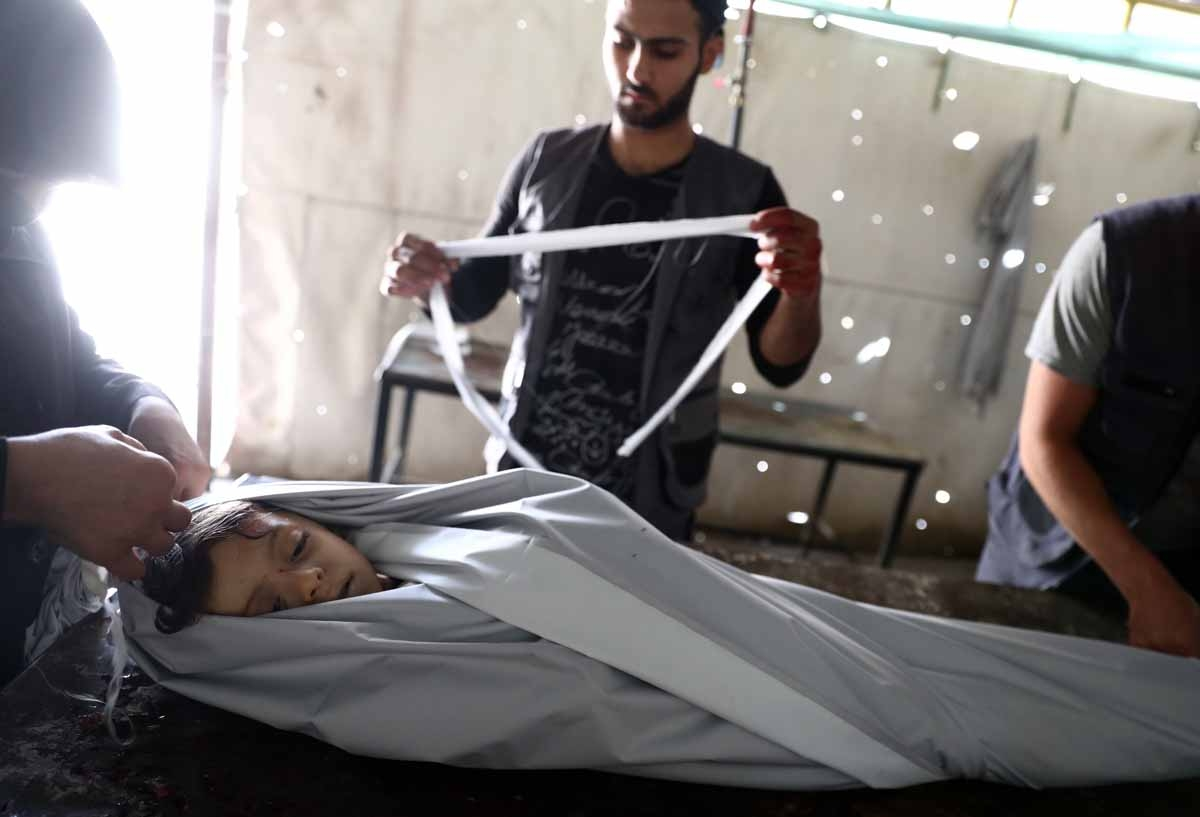 Volunteers wrap in shrouds the body of a Syrian child, Emad, 5, at a makeshift morgue following a reported air stike on the rebel-held town of Douma, east of the capital Damascus, on August 23, 2016.