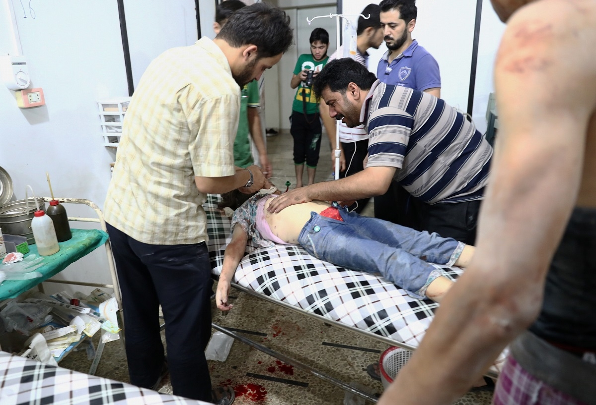 A Syrian man stands next to his daughter as she receives treatment at a makeshift hospital following a reported air stike on the rebel-held town of Douma, east of the capital Damascus, on August 23, 2016.