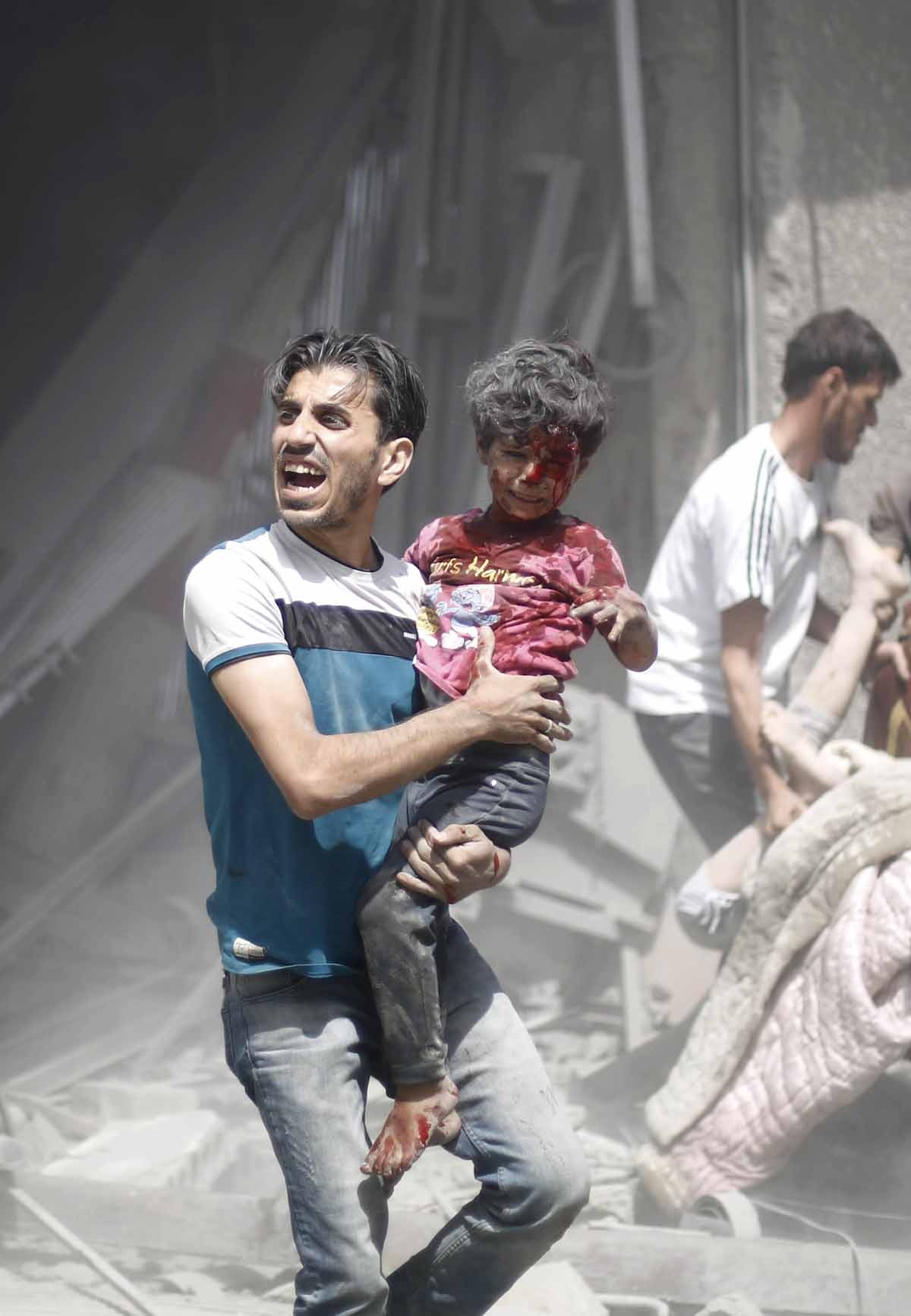 A Syrian man carries a wounded child following a reported air strike by Syrian government forces in the rebel-held area of Douma, east of the capital Damascus, on August 30, 2015.