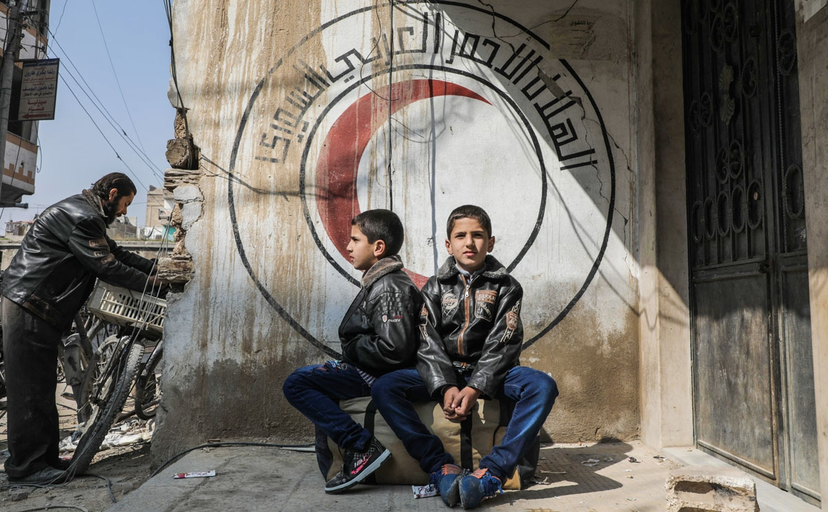 Syrian children sit on a luggage bag before a mural on a wall bearing the logo of the Syrian Red Crescent at the organisation's branch in Douma in the rebel-held enclave of Eastern Ghouta on the eastern outskirts of the capital Damascus on March 13, 2018,