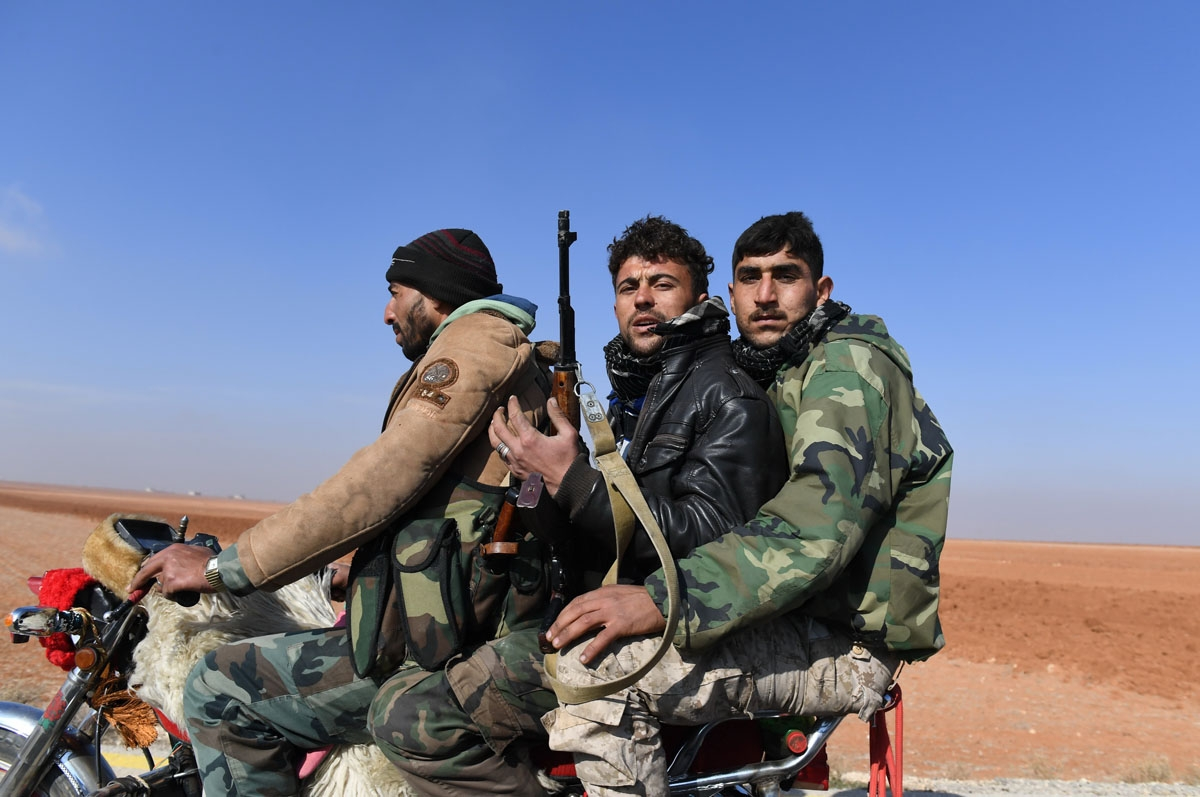 Members of the Syrian government forces drive a motorbike in the village of al-Hajib, near Jabal al-Hass, in the southern part of Aleppo province as they advance with the aim of capturing the Abu Duhur military airport in the ongoing offensive against opp