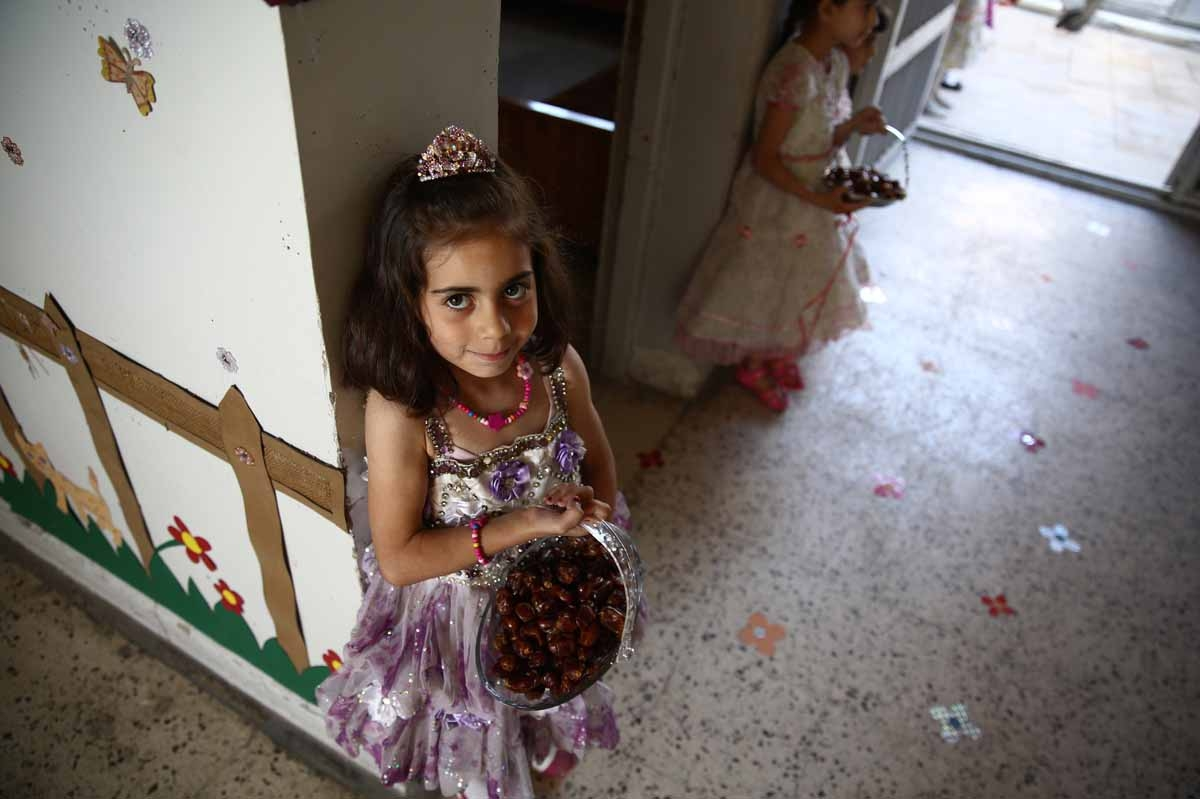Syrian school girls carry baskets with dates at the entrance of the Saif al-Dawla school as they take part in activities surrounding an art competition organised as part of a local initiative to shift the children's minds from the atrocities of the Syrian