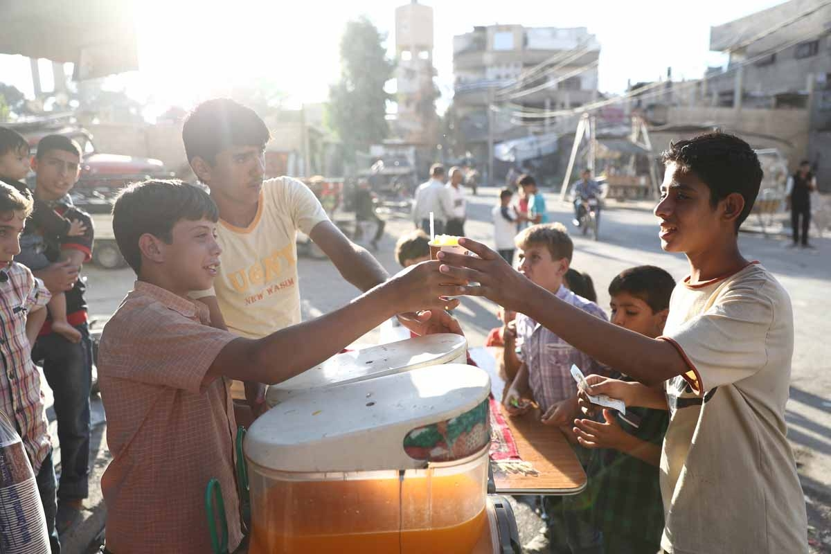 A Syrian boy serves a juice on the third day of the Al-Adha Eid (Festival of Sacrifice) Muslim holiday in the rebel-controlled town of Hamouria, in the eastern Ghouta region on the outskirts of the capital Damascus, on the second day of an internally back