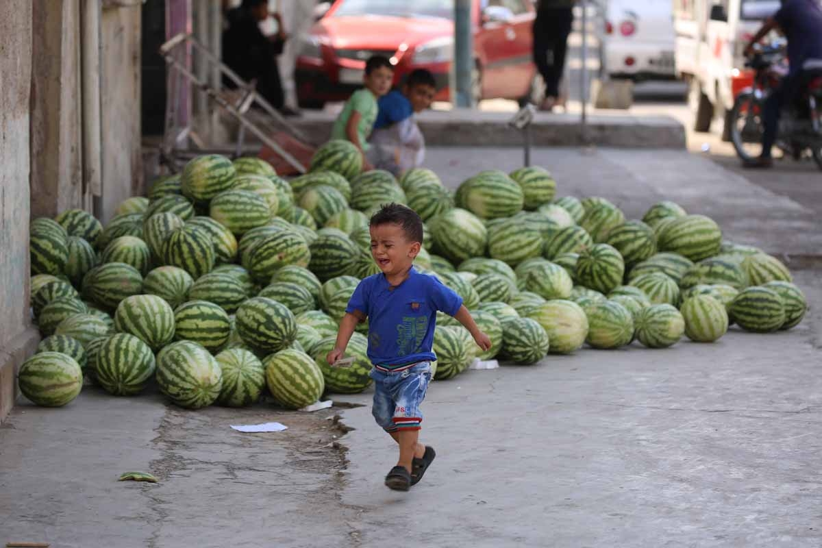 A Syrian child walks past watermelons displayed for sale along on a street in the Kurdish-majority northeastern city of Qamishli on September 16, 2016