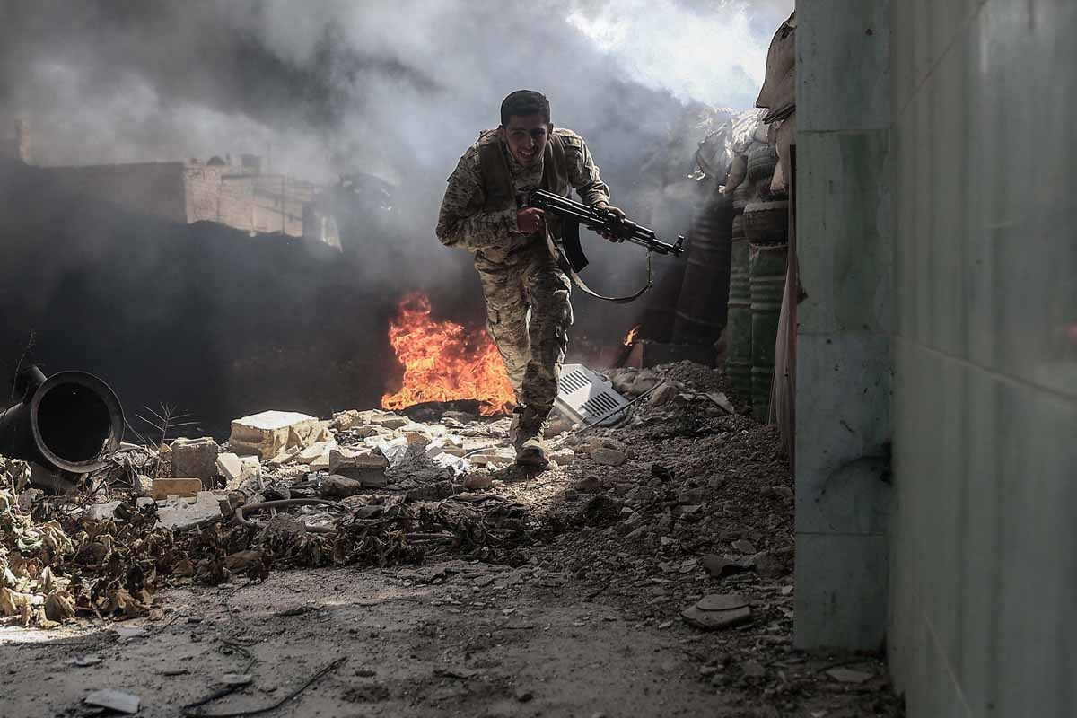 A fighter from the Jaish al-Islam (Islam Army) runs to avoid sniper fire, in the village of Tal al-Siwan area of the rebel-held stronghold of Douma, on the outskirts of Damascus, on September 5, 2016.