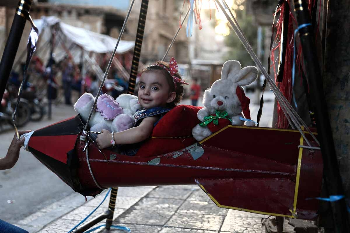 A Syrian child plays on a swing, made from the remnants of exploded rockets in the rebel-held town of Douma, on the eastern edges of the capital Damascus, on September 14, 2016, on the third day of Eid al-Adha Muslim holiday.
