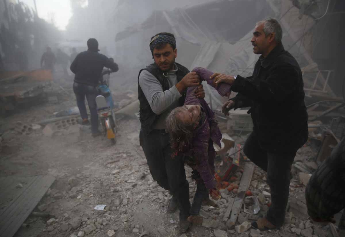 Men evacuate the body of a girl from under the rubble following reported airstrikes on the town of Hamouria in the eastern Ghouta region, a rebel stronghold east of the Syrian capital Damascus, on December 9, 2015.