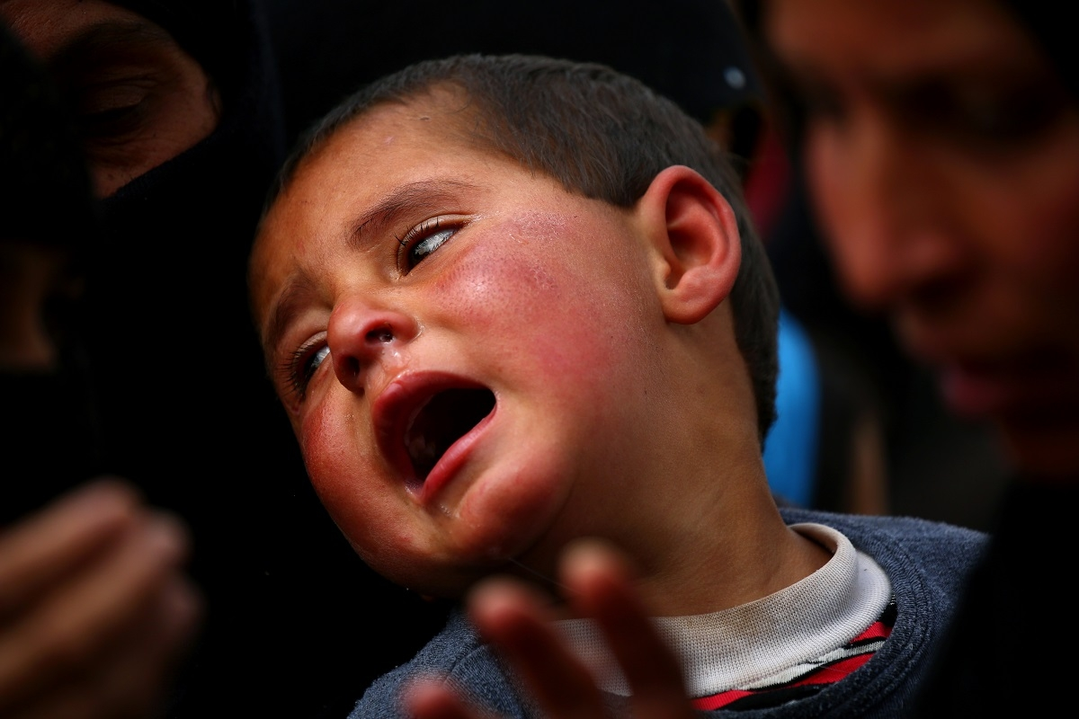 A boy reacts as displaced Syrians from Tabqa and Raqa, who fled the fighting between the US-backed Syrian Democratic Forces and Islamist State group jihadists, wait for receiving aid parcels near the northern Syrian village of Jarniyah, on April 6, 2017.
