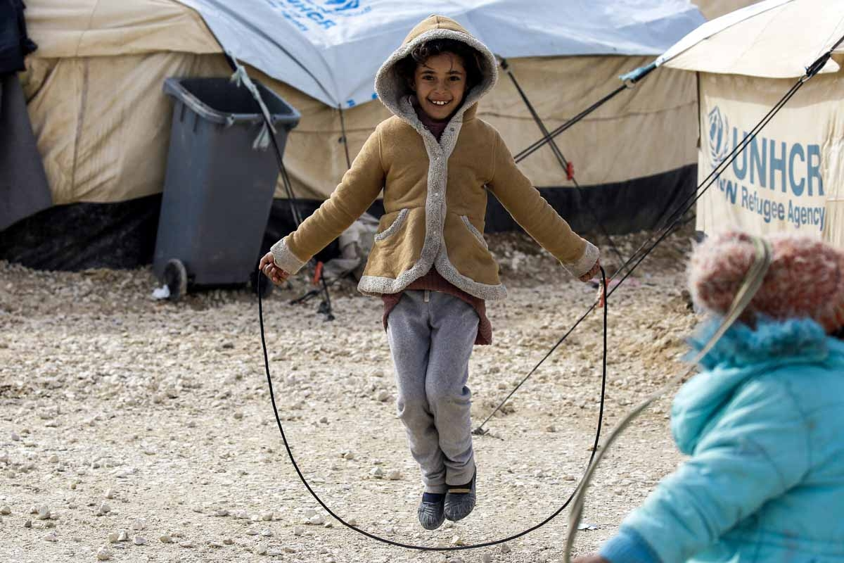 A displaced Syrian child, fleeing from Deir Ezzor city besieged by Islamic State (IS) group fighters, skips on a rope in a refugee camp in al-Hol, located some 14 kilometers from the Iraqi border in Syria's northeastern Hassakeh province, on February 1, 2